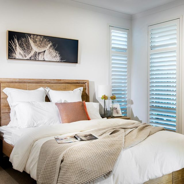 White bedroom with long white shutters